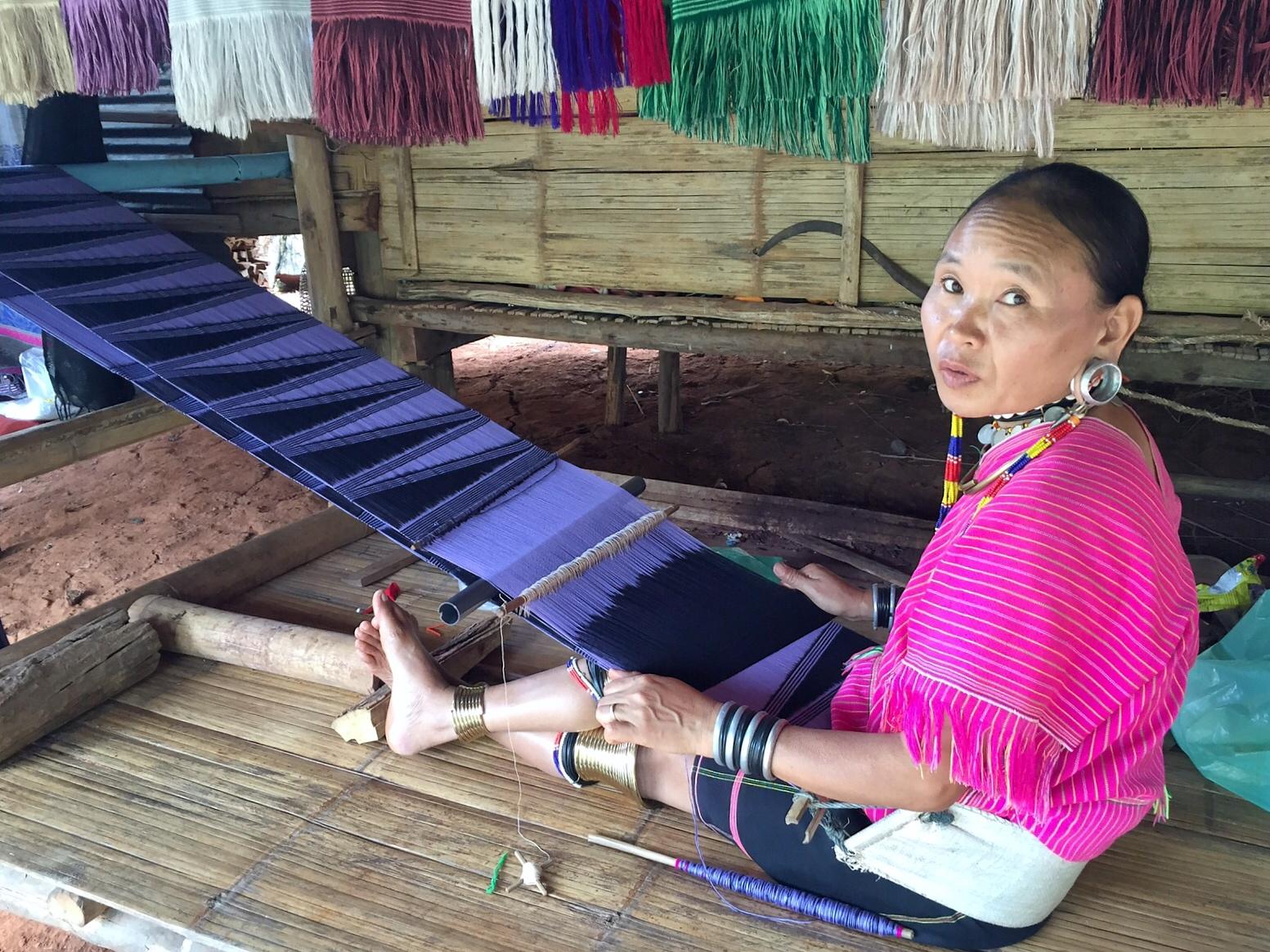 a long neck woman is weaving